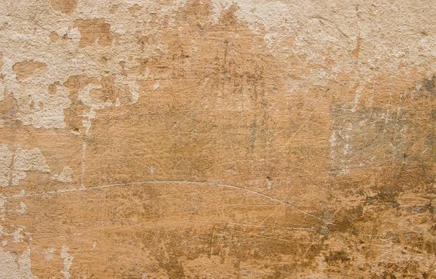 Бетонная стена покрыта бежевым облицовочным наполнителем. на старой стене царапины и потертости разных размеров.