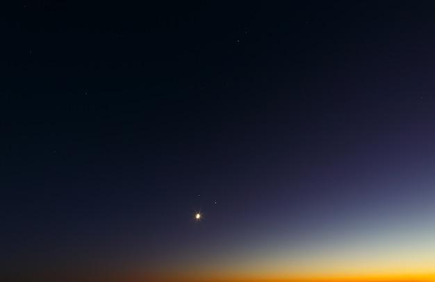 冬の月、木星、土星の合体。日没後の明るい夕方の空。
