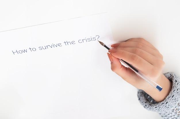 Последствия пандемии коронавируса. женские руки пишут на листке бумаги, как пережить кризис