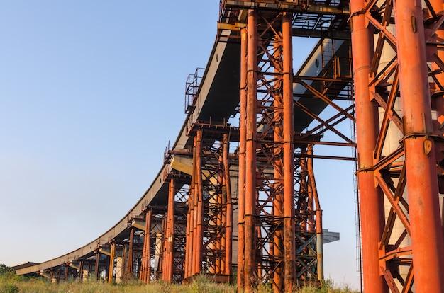 Строительство моста через реку с опорами, конструктивными элементами, кранами.