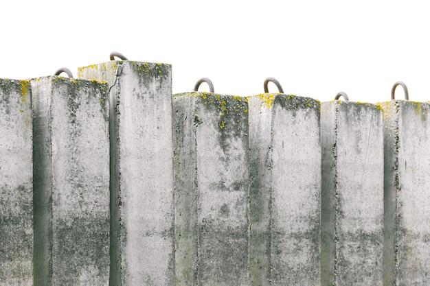 Строительство грязных бетонных блоков со мхом в ряд укрепляет берег реки.