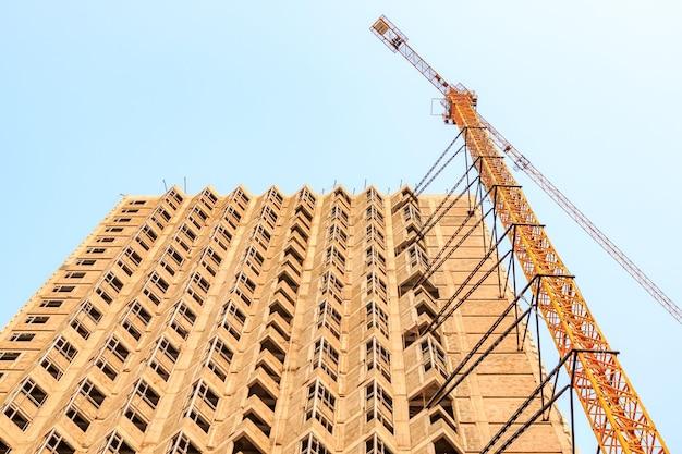 オフィスフロアとショッピングセンターを備えた高層マンションまたはホテルの建設プロセス。タワークレーンは、青空を背景に建物本体に取り付けられています。