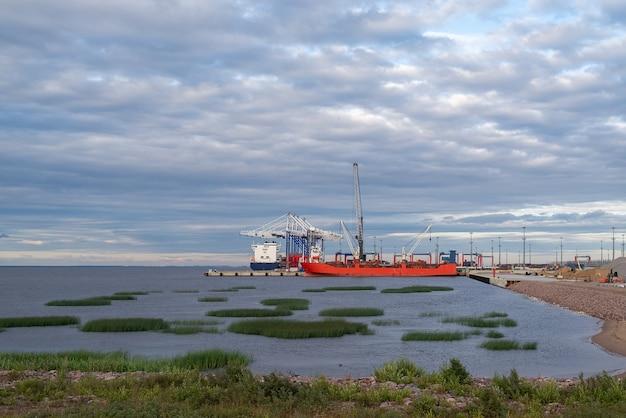 コンテナ船は川の貨物港に積み込まれています自然光