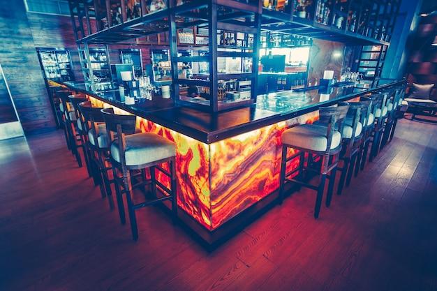장비를 갖춘 현대적인 바 카운터와 현대적인 레스토랑의 편안한 바 의자. 세련된 내부 장식. 진한 파란색과 빨간색의 조합입니다.