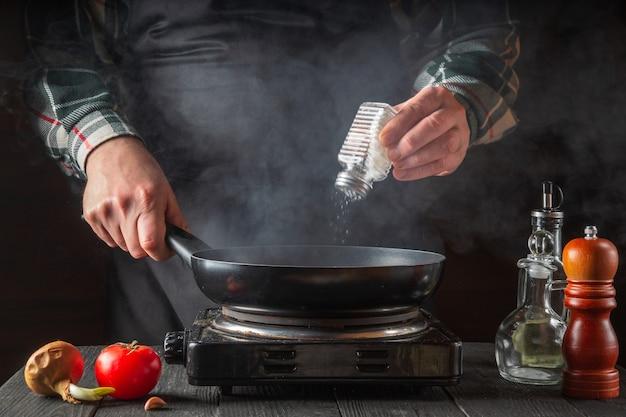 Повар добавляет соль, готовя еду на сковороде.