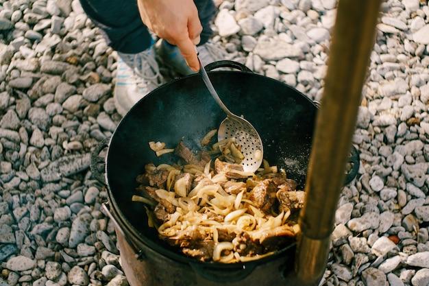 Повар готовит плов в казане на открытом огне на улице, помешивая большим черпаком.