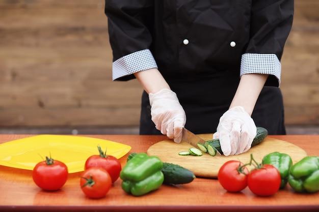 料理人はテーブルの上で夕食のために新鮮な農場の野菜を切ります