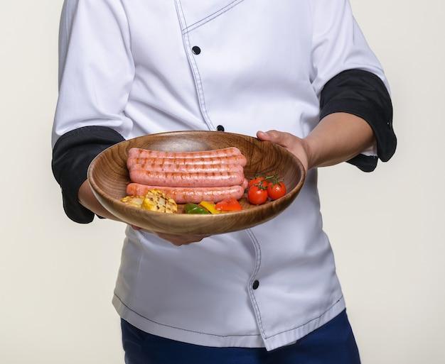 요리사는 튀긴 소시지의 기성품 요리를 들고