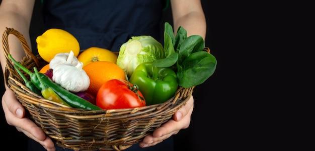요리사는 야채와 과일 바구니를 들고 있습니다. 요리 . 건강한 식생활 훌륭한 음식. 채식주의 자 음식. 배너. 음식 배경입니다.