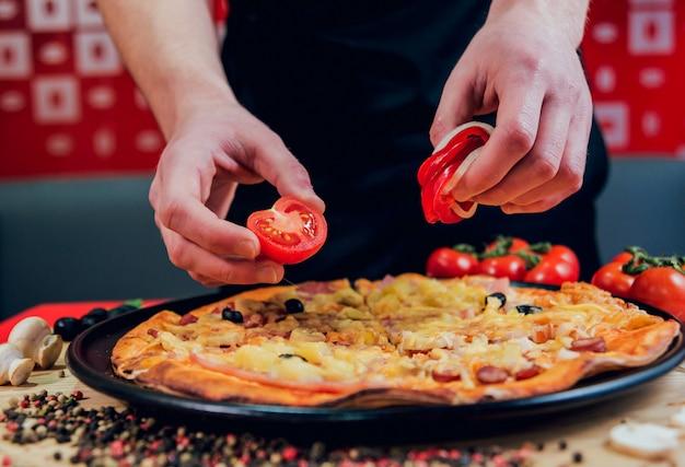 요리사가 피자를 만들고 있습니다. 재료를 추가합니다.