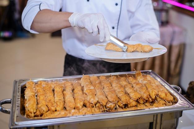 Повар ставит тарелку куриного шашлыка