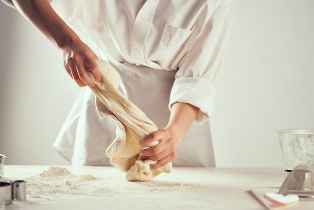 Повар раскатывает тесто кондитер из муки своими руками