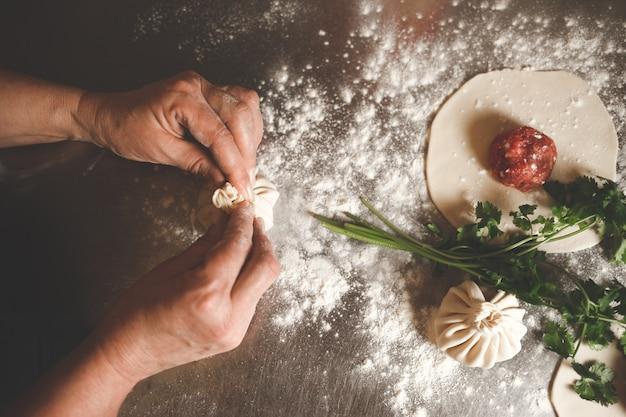 요리사는 원래 그루지야 요리법에 따라 킨 칼리를 조각합니다.
