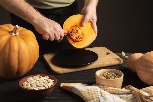 요리사는 반으로 자른 호박에서 곡물을 분리합니다. 검은 나무 테이블에는 크기가 다른 전체 호박이 있습니다. 두 그릇에 씨앗.