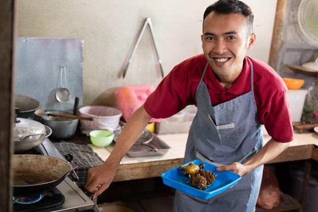 屋台で客のためにおかずを揚げるためにストーブをつけたとき、料理人は微笑んだ。