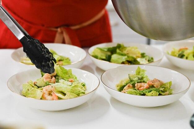コックは調理されたサラダを広げます