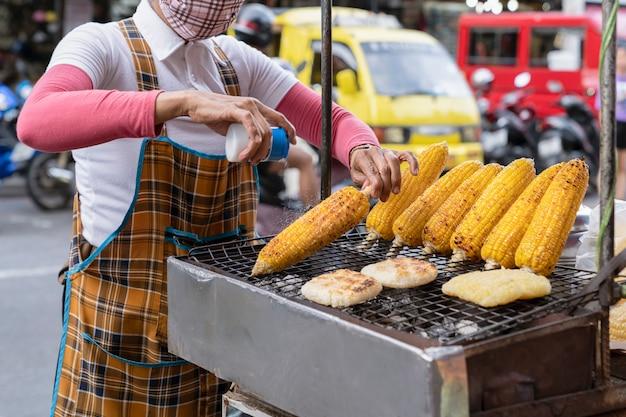 요리사는 갓 구운 옥수수에 소금을 뿌린다. 아시아, 태국에서 길거리 음식