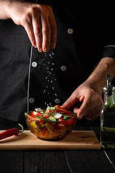 Повар посыпает салат из соленых свежих овощей в тарелке на деревянном столе.