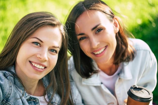 素晴らしい一日の涼しい気分。屋外でカジュアルな服を着た2人の美しい若いガールフレンドのselfie写真を閉じる