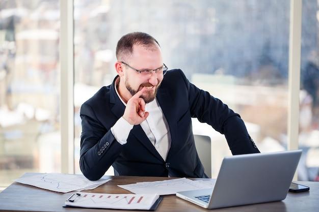 회사 미친 사람은 사무실에 있는 컴퓨터에 앉아 미쳐가고 있습니다. 탁자에 있는 남자의 감정적 초상화입니다. 그의 직장에서 미친 노동자