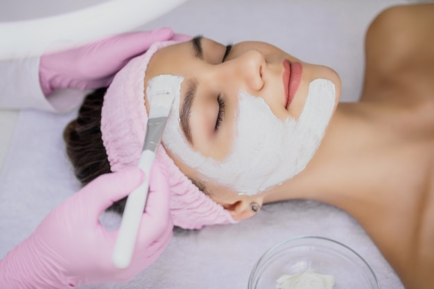 美容師は白いブラシで女の子の顔に白い粘土のマスクを適用します