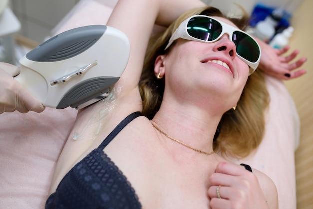 Косметолог проводит процедуру лазерной эпиляции в зоне подмышек