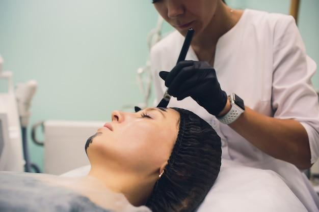 Косметолог в розовых перчатках с кисточкой наносит карбоновую маску для пилинга лица молодой девушки в косметологическом кабинете. концепция косметологических услуг и ухода за собой.