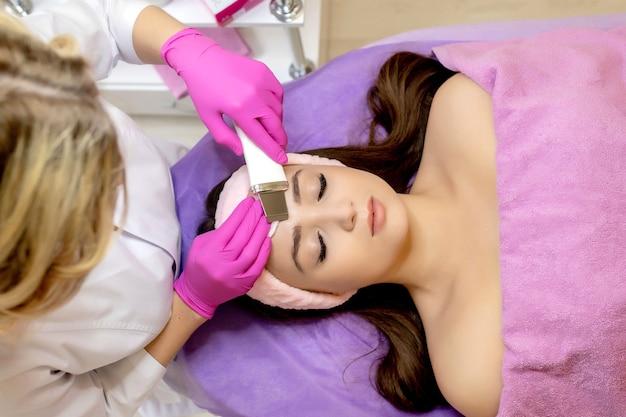 美容師は、美容院で美しい若い女性の顔の皮膚の超音波フェイスピーリングの手順を行います。
