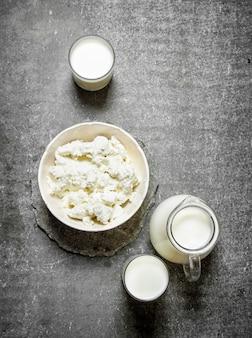 ボウルにカッテージチーズと石のテーブルにミルク