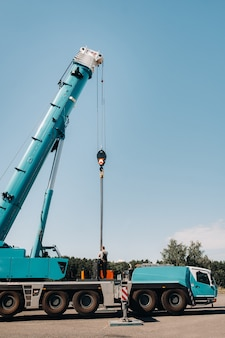 Противовес установлен неузнаваемым рабочим на большой синий автомобильный кран и подготовлен к работе на участке рядом с большим современным зданием.