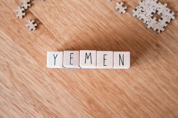 木製の背景、中東の国の木製キューブに書かれたイエメン国