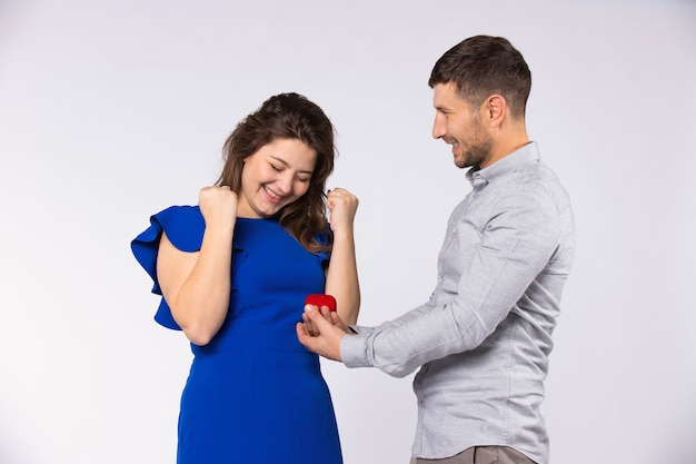 Достижение пары. мужчина сделал девушке предложение и подарил обручальное кольцо на день всех влюбленных. серый фон.