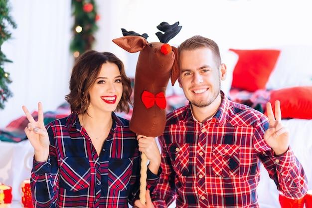 Пара и олени стоят между ними, они смотрят в объектив камеры и смеются