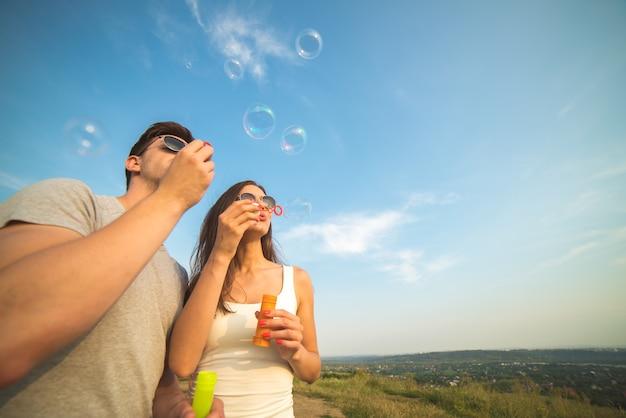 Пара пускает мыльные пузыри на фоне голубого неба
