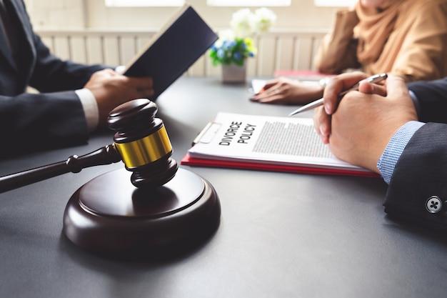 Пара консультирует адвоката по поводу соглашения о разводе.
