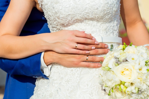 Пара обнимается и держит букет невесты. руки крупным планом.