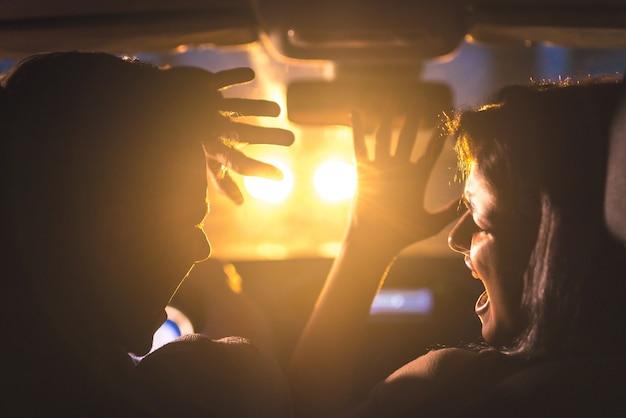 カップルは緊急事態で車を運転します。夕方の夜
