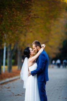 秋の木々の背景に優しくキスをするカップル