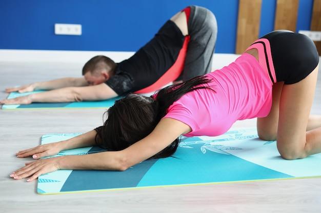 Пара занимается спортом в домашнем тренажерном зале, упражнениями на растяжку. поза йоги, снятие стресса. поддержка здорового образа жизни.