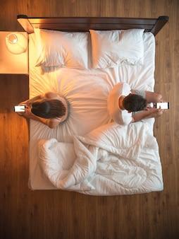 Пара держит телефоны на кровати. вид сверху