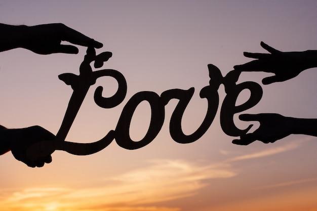 カップルは木製の愛の碑文を手に保持します