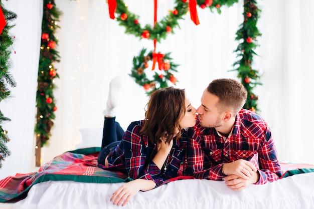 Влюбленная пара ложится на кровать и целуется.