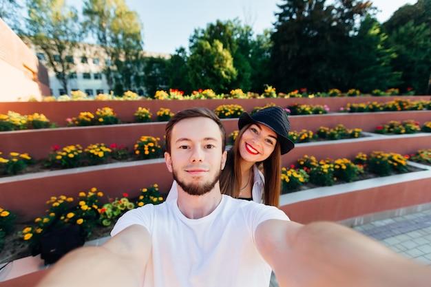 愛するカップルは、マルチレベルの花壇の背景にセフィーを作ります