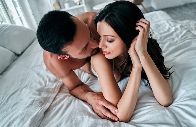 ベッドに横たわっている下着のカップル
