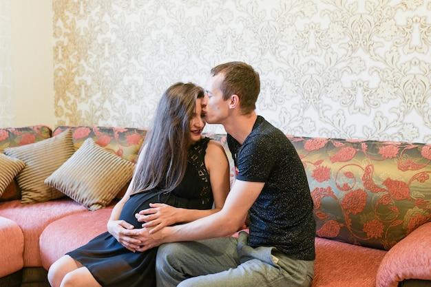 부부는 아기를 기다리고 있습니다. 사랑하는 임신 부부는 침대에 누워, 껴안고, 아기를 기대
