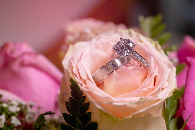 カップルのダイヤモンドの結婚指輪は、結婚式の日にピンクのバラの上に置かれます。