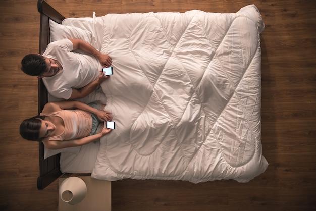 カップルはベッドと電話に座っています。上からの眺め