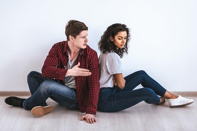 Пара сидит на полу и ссорится