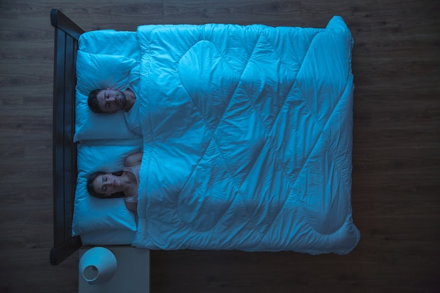 Пара спит на кровати. вечер в ночное время. вид сверху