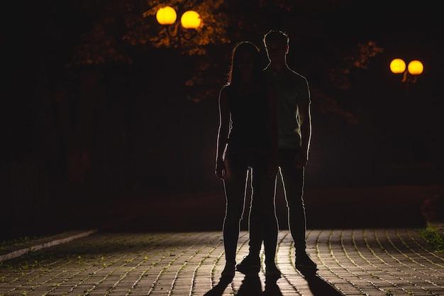 Пара стоит в темном переулке. ночное время